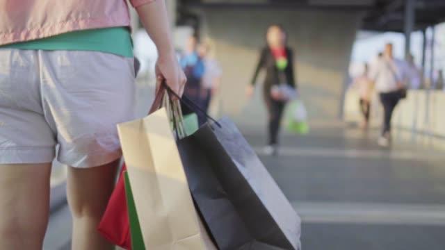 frau spaziert mit einkaufstaschen, slow motion - carrying stock-videos und b-roll-filmmaterial