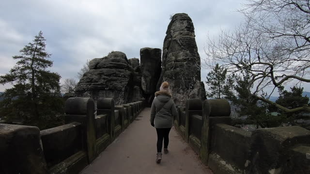 Woman walking with winter jacket and hat in the bridge of the beautiful Saxon National Park in Germany with stunning views of the rock formations during travel vacations.