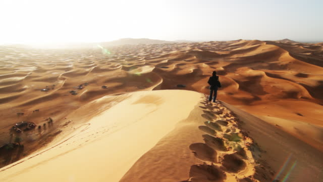 Woman walks a sand dune.