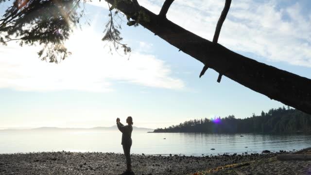 Woman walks across beach under tree, takes smart phone pic