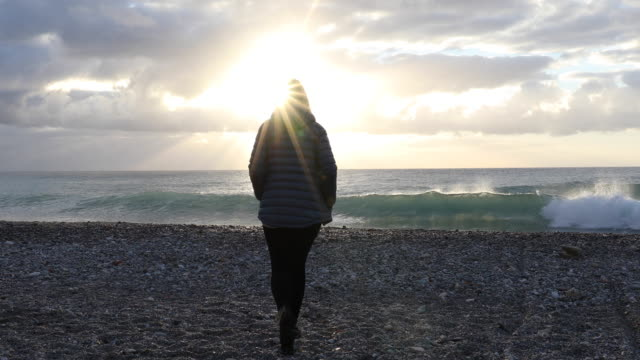 woman walks across empty beach, looks to sea, sunrise - down jacket stock videos and b-roll footage