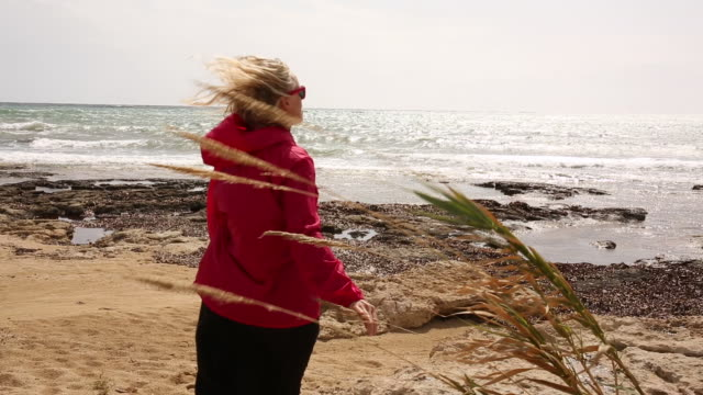 woman walks across empty beach on windy day - only mature women stock videos & royalty-free footage