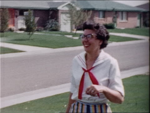 a woman walks across her front yard and smiles. - 1950 stock videos & royalty-free footage