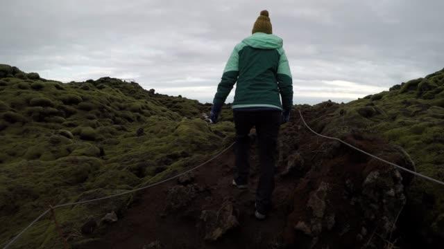 vídeos de stock, filmes e b-roll de mulher atravessa o campo de lava cobertas de musgo - só uma mulher de idade mediana
