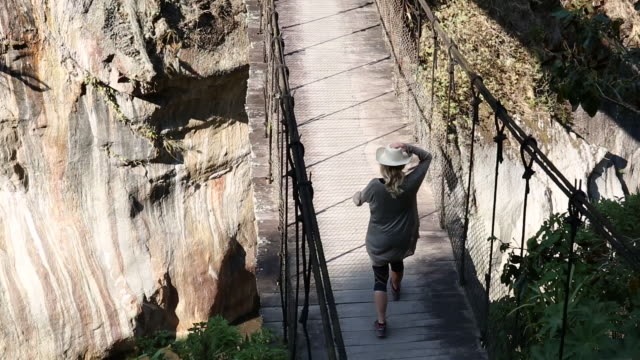 woman walks across suspension bridge, above gorge - only mature women stock videos & royalty-free footage