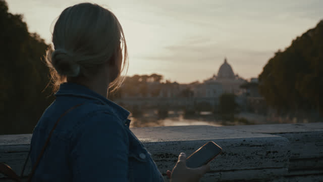 slo mo女性は橋を渡って歩き、日没時にサンタンジェロ橋の景色を楽しむ - ラツィオ州点の映像素材/bロール