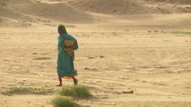 a woman walks across the desert landscape at nuri in sudan.  - copricapo abbigliamento video stock e b–roll
