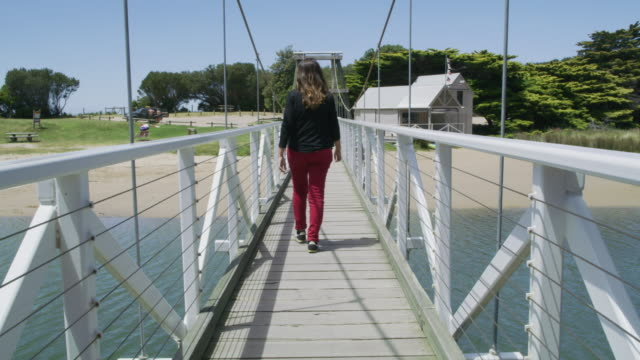 ws a woman walks across the swing bridge / lorne, australia - swing bridge stock videos & royalty-free footage