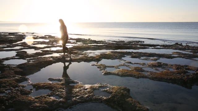 woman walks across tidal pools, rising sun behind - tidal pool stock videos and b-roll footage
