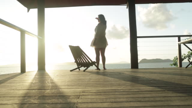 Woman walks across veranda and looks out to sea then sits in chair.