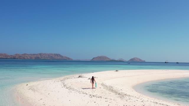 woman walks alone on deserted island - desert island stock videos & royalty-free footage