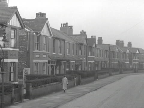 a woman walks along a typical suburban street in manchester - bbc archive stock-videos und b-roll-filmmaterial