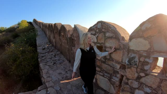 woman walks along ancient fort wall at sunrise - surrounding wall stock videos & royalty-free footage