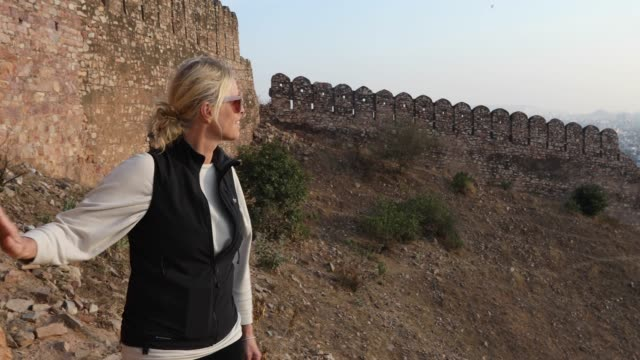 woman walks along ancient fort wall at sunrise - history stock videos & royalty-free footage