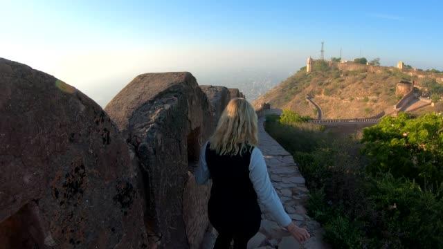 stockvideo's en b-roll-footage met vrouw wandelingen langs de muur van het oude fort bij zonsopgang - alleen één oudere vrouw