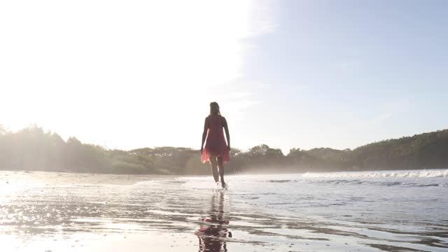 woman walks along beach along surf edge - barefoot stock videos & royalty-free footage