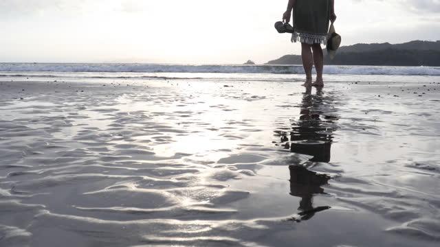 vidéos et rushes de woman walks along beach, into sunrise - une seule femme d'âge mûr
