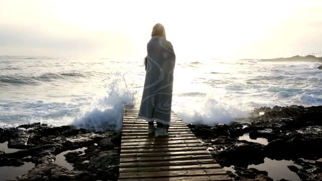 Woman walks along boardwalk above sea, wrapped in blanket