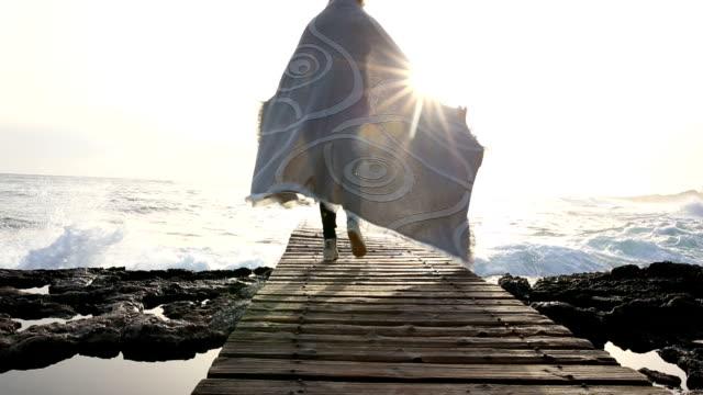 frau geht am boardwalk über dem meer in decke gewickelt - eingewickelt stock-videos und b-roll-filmmaterial