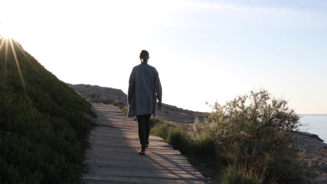 Woman walks along boardwalk at sunrise
