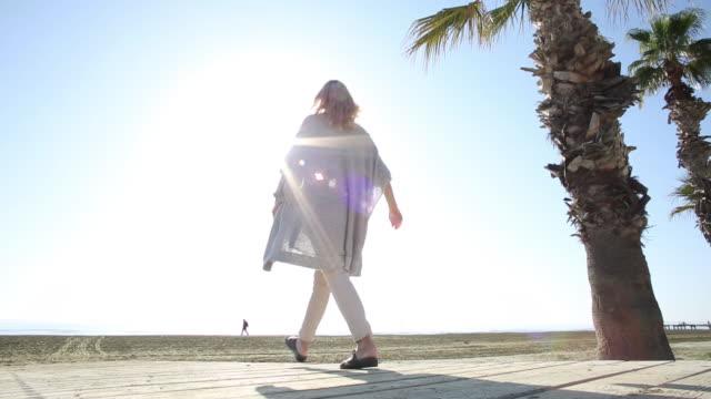 woman walks along boardwalk to empty beach - boardwalk stock videos & royalty-free footage