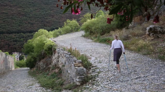 woman walks along cobblestone corridor, using hiking poles - hiking pole stock videos & royalty-free footage