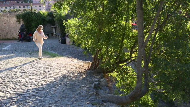 woman walks along cobblestone path, looks out over village - kletterausrüstung stock-videos und b-roll-filmmaterial