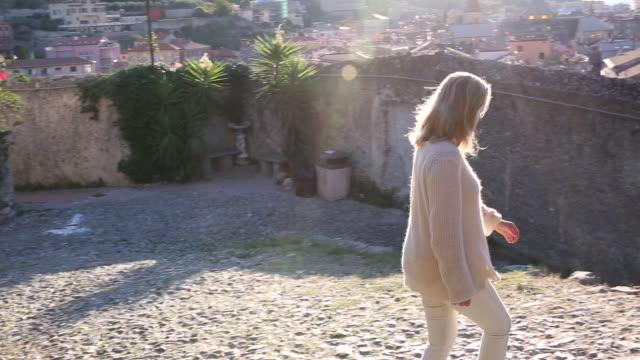 Woman walks along cobblestone path, looks out over village