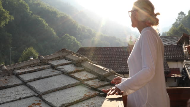woman walks along deck, looks out to mountain landscape - slate rock stock videos and b-roll footage
