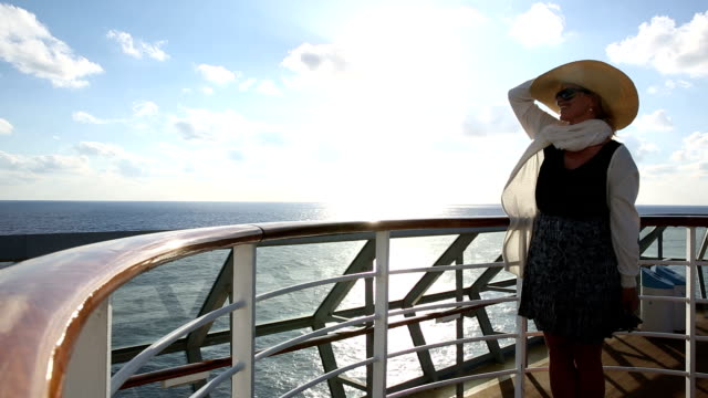 woman walks along deck railing, above mediterranean sea - cruise stock videos and b-roll footage