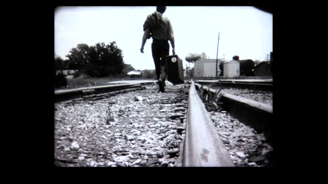 1968 woman walks along desolate train track, man carries suitcase along train track. - decisions stock videos & royalty-free footage