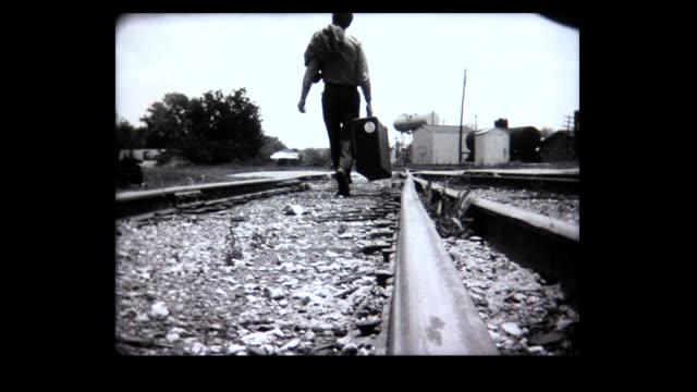 vidéos et rushes de 1968 woman walks along desolate train track, man carries suitcase along train track. - désespoir