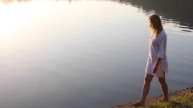 Kvinnan promenader längs kanten av sjön, vid soluppgången