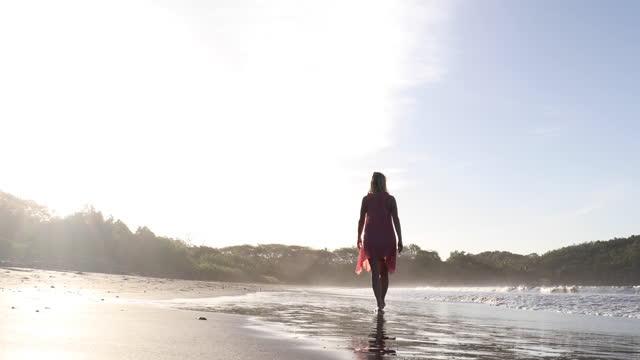 vidéos et rushes de le femme marche le long de la plage vide au lever du soleil, au bord de surf - 60 64 ans