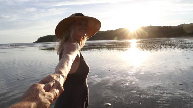 vídeos y material grabado en eventos de stock de woman walks along empty beach, reaches for man's hand - coquetear