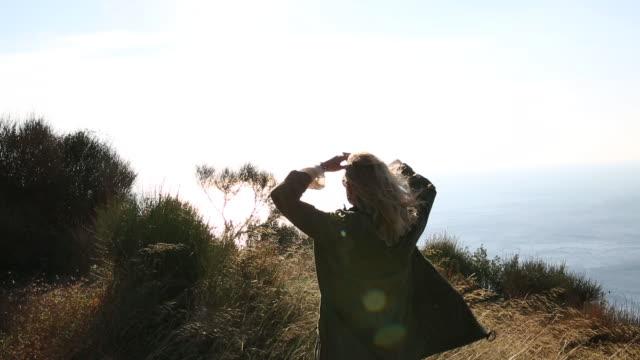 woman walks along grassy bluff overlooking sea - casacca video stock e b–roll