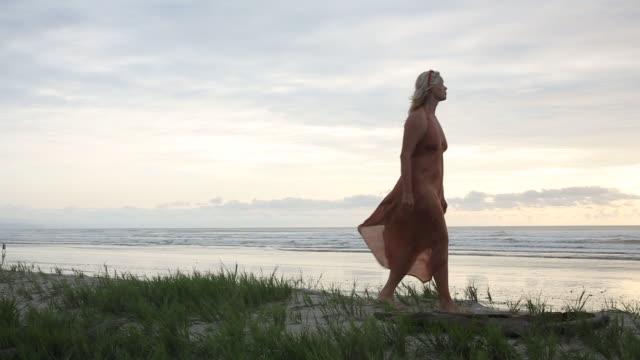 woman walks along grassy crest above beach at sunrise, holding feather - オオハマガヤ属点の映像素材/bロール