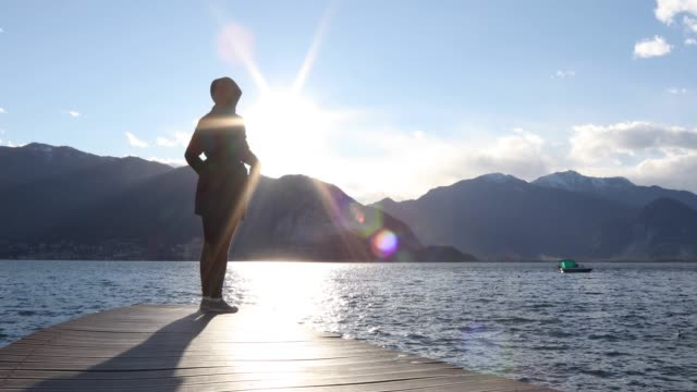 woman walks along lake pier at sunrise - legs crossed at ankle stock videos & royalty-free footage