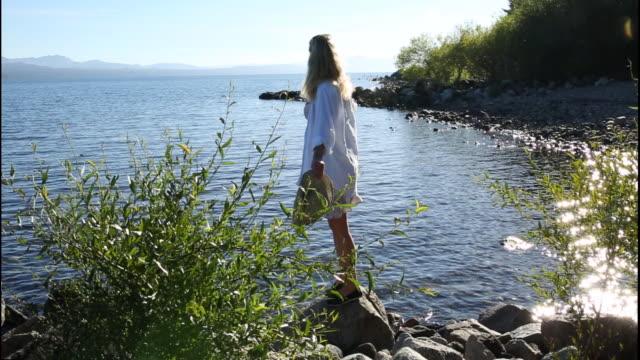 日の出の湖沿いを歩く女性 - 全身点の映像素材/bロール