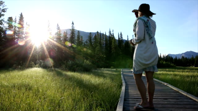 Frau geht am mountain-Promenade in Richtung Sonnenaufgang