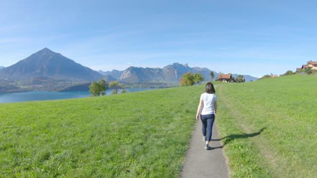 woman walks along pathway through green meadow - leggings stock videos & royalty-free footage