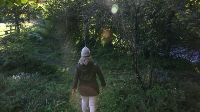 Woman walks along pathway through rural forest
