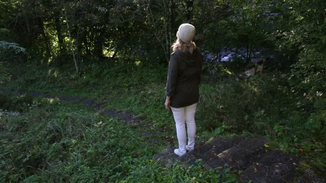 woman walks along pathway through rural forest - 段点の映像素材/bロール
