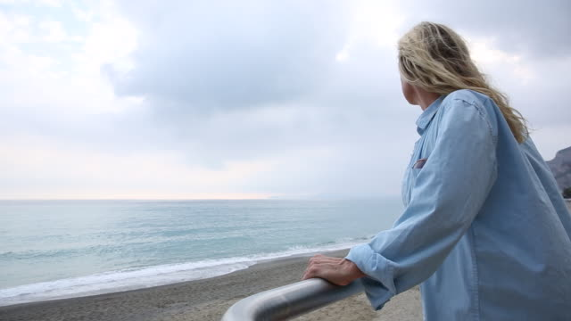 stockvideo's en b-roll-footage met woman walks along railing and looks out over the sea - hemden en shirts