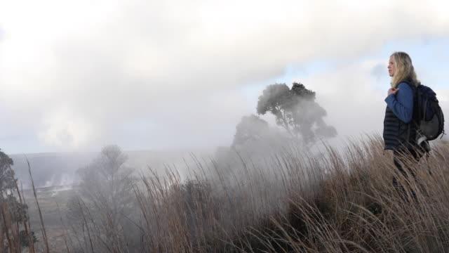 woman walks along ridge crest, in meadow - mature women stock videos & royalty-free footage