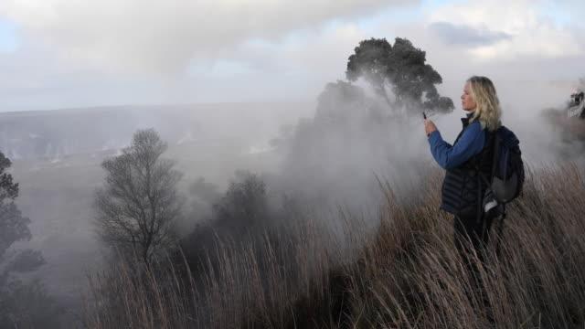 vídeos y material grabado en eventos de stock de woman walks along ridge crest, in meadow - isla grande de hawái islas de hawái