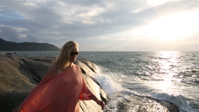 woman walks along rock slabs above sea, looking off - sarong stock videos & royalty-free footage