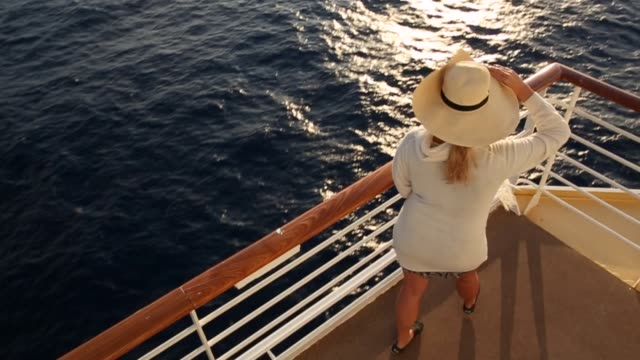 woman walks along ship deck at sunrise - ponte di una nave video stock e b–roll
