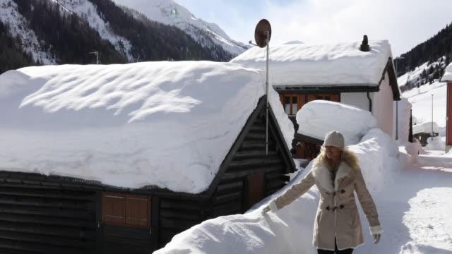 woman walks along snowy corridor through village - village stock videos & royalty-free footage
