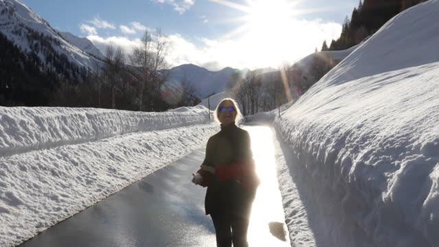 frau auf verschneiten weg geht, wirft schneeball in die kamera - wintermantel stock-videos und b-roll-filmmaterial